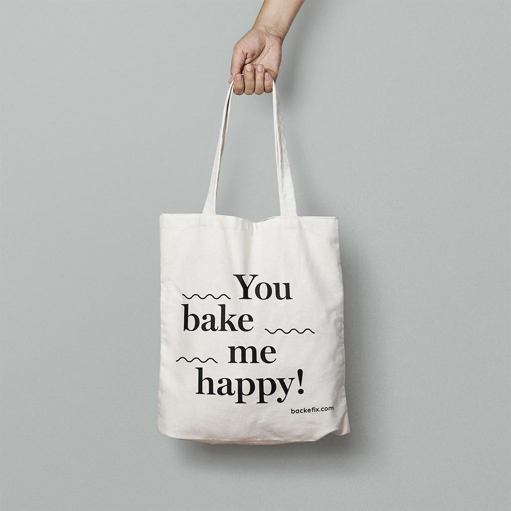 Hand trägt Baumwolltasche Motiv You bake me happy