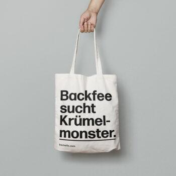 Hand trägt Baumwolltasche Motiv Backfee sucht Krümelmonster.